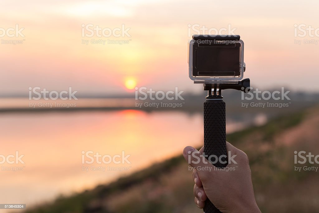 hand holding extreme camera take photo during sunset stock photo