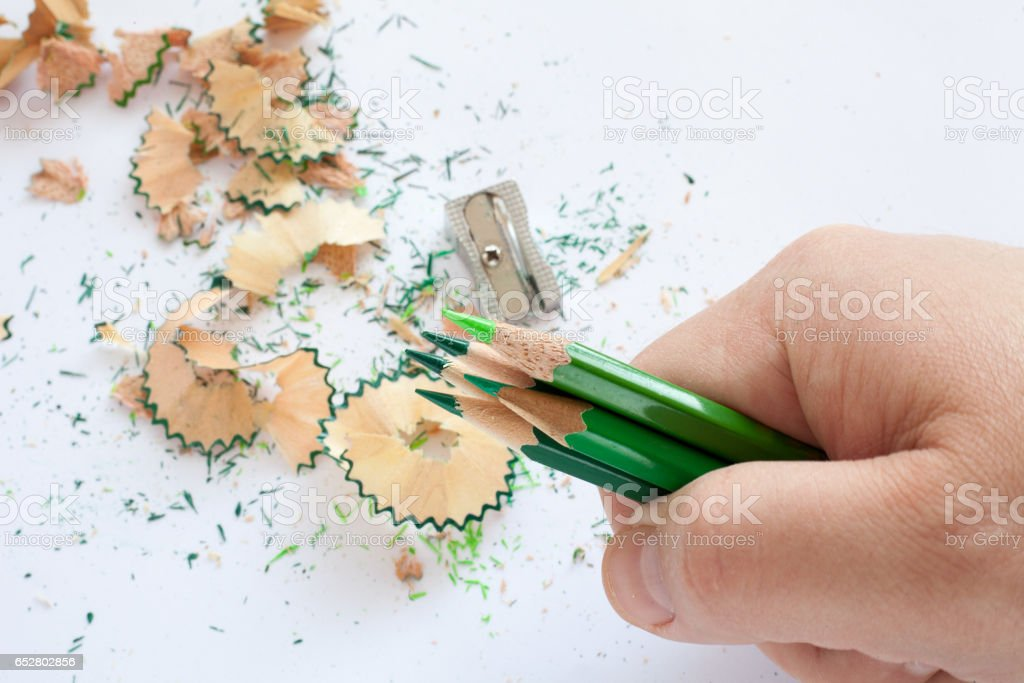 Hand holding five green wooden pencils stock photo