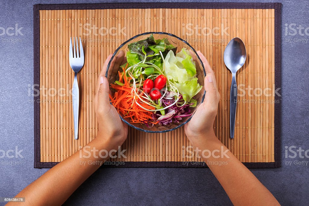 Hand holding fresh salad bowl stock photo