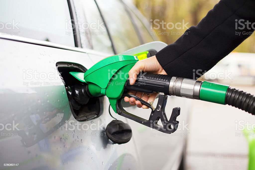 Hand holding fuel pump and refilling car at petrol station stock photo