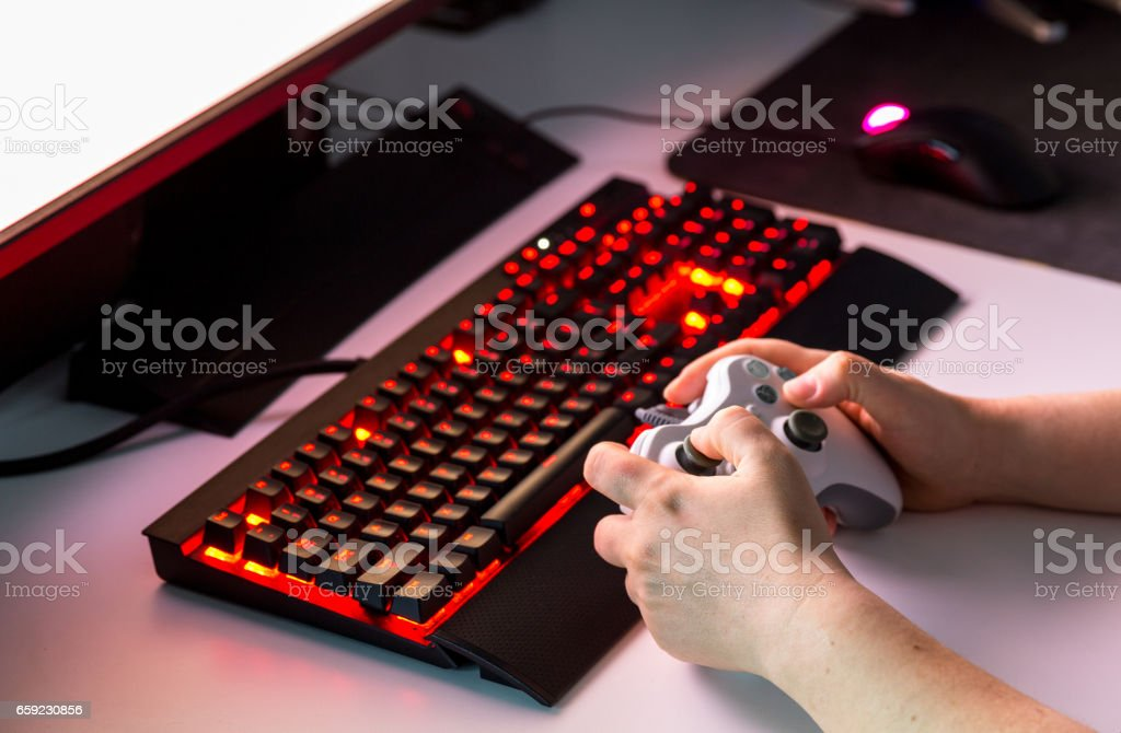 Hand holding game console controller playing game on the display stock photo
