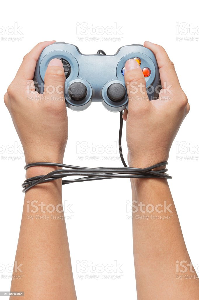 hand holding game controller and tied up with cables stock photo