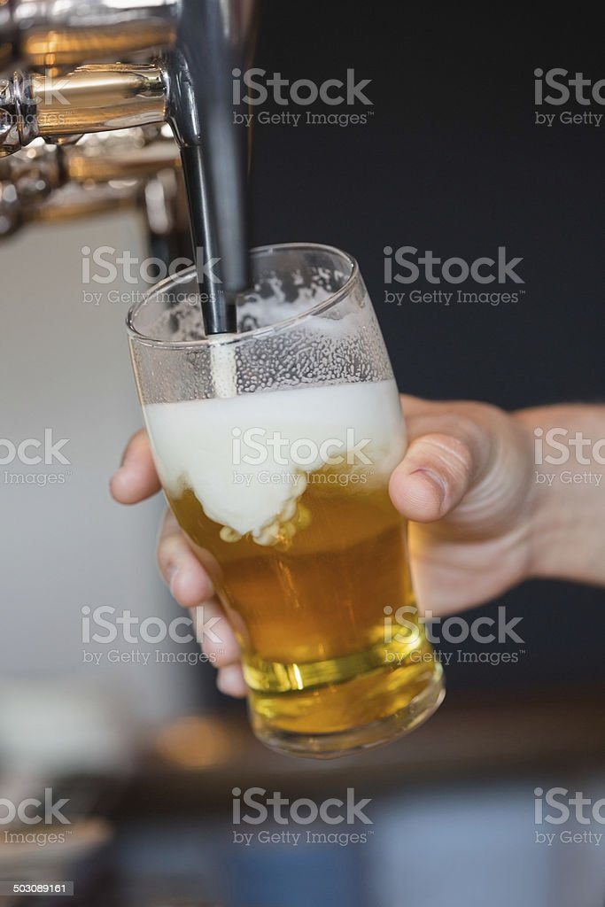 Hand holding glass filling beer stock photo
