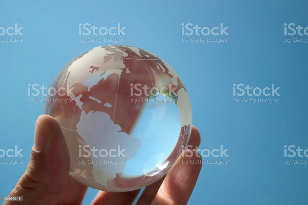Hand holding globe model on blue background  stock photo