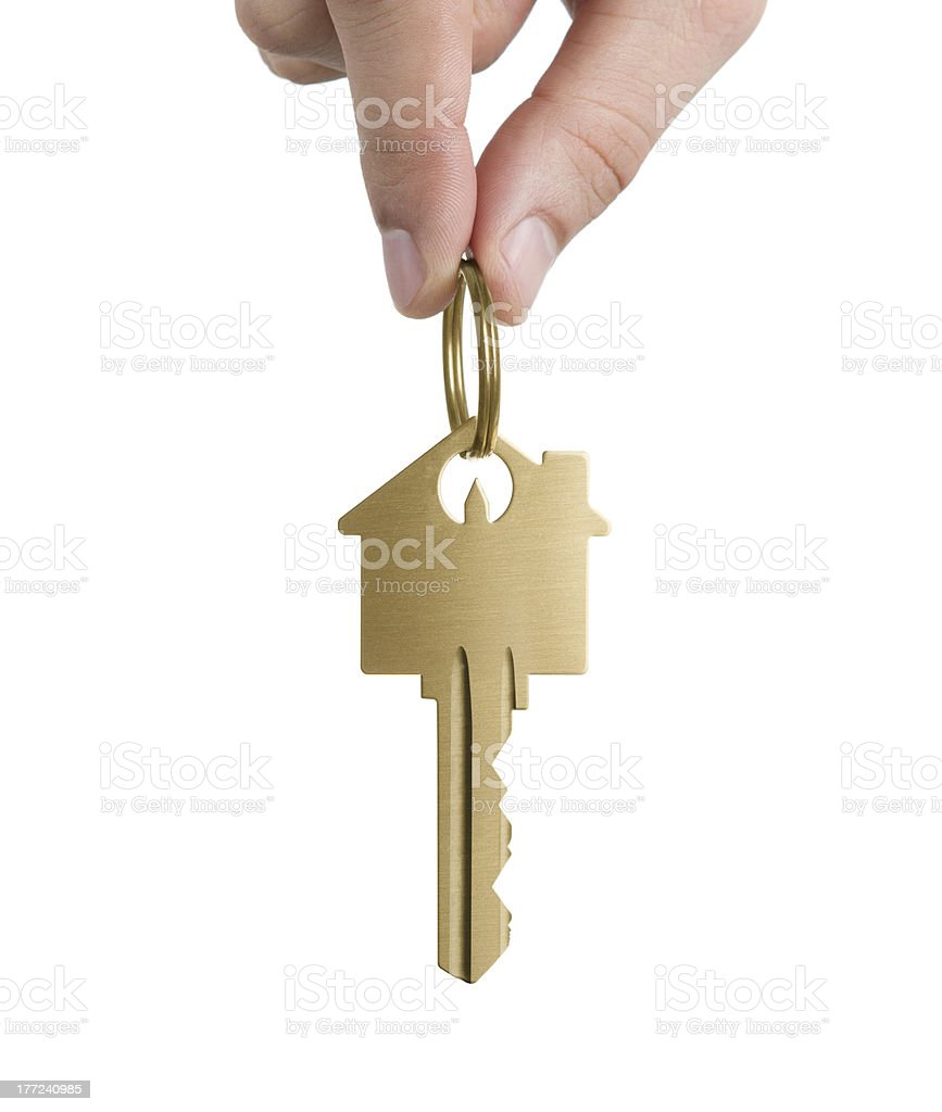 Hand holding gold house shaped key stock photo
