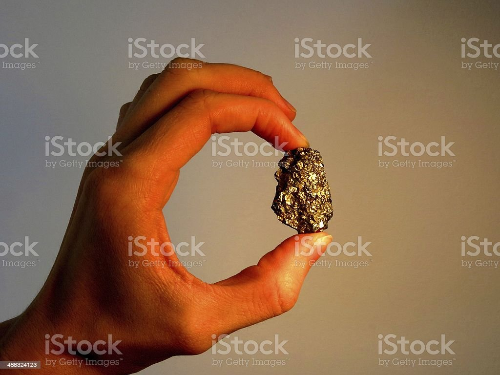 Hand Holding Gold Nugget stock photo