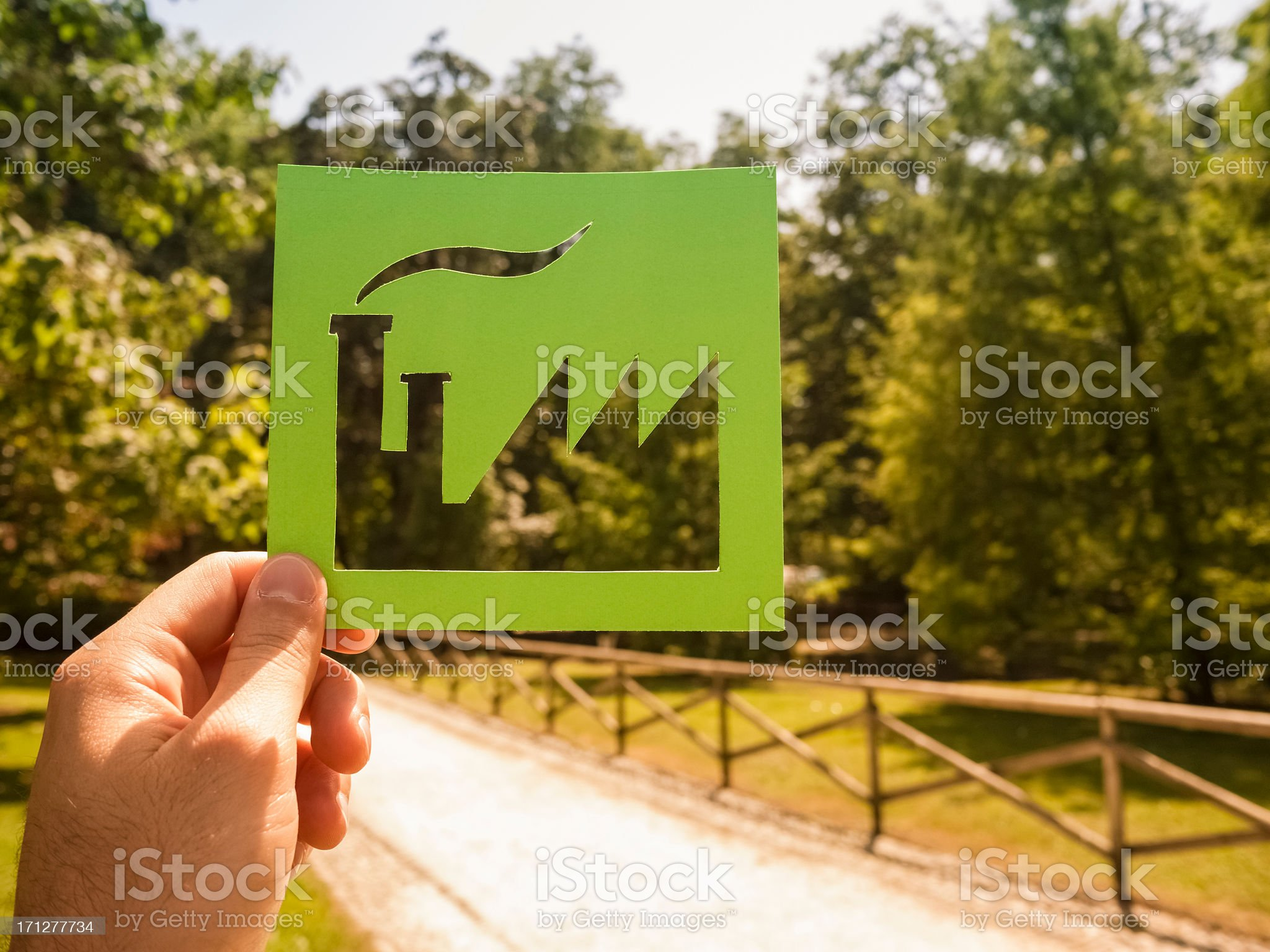 Hand holding green factory against a path in the park royalty-free stock photo