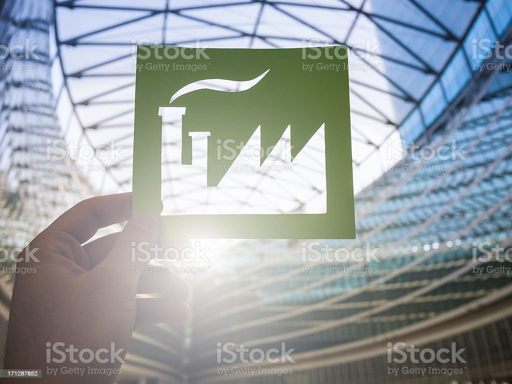 Hand holding green factory against modern architecture royalty-free stock photo