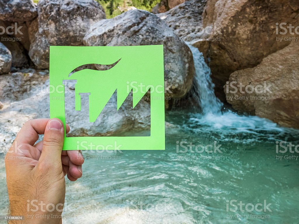 Hand holding green factory against waterfall royalty-free stock photo