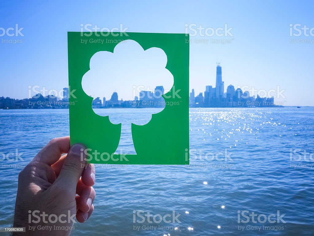 Hand holding green tree against the city stock photo
