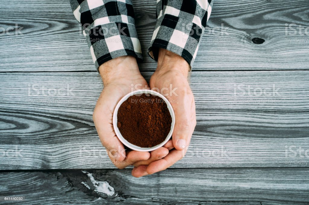 Hand Holding Ground Coffee stock photo