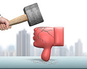 Hand holding hammer hitting red thumb down with cracks