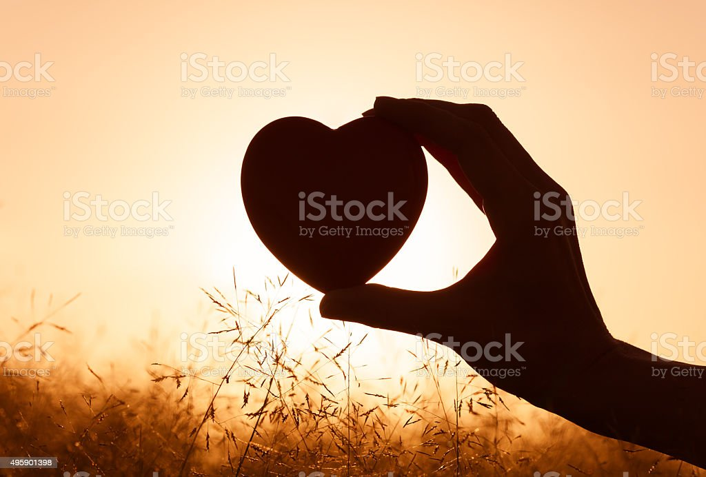 Hand holding heart against beautiful setting. stock photo