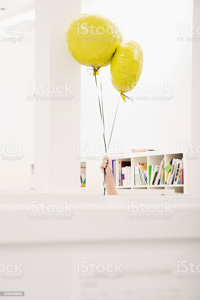 Hand holding helium balloons in office stock photo