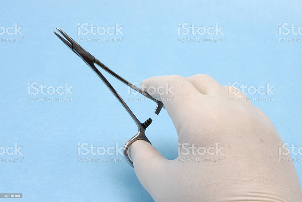 Hand holding hemostat stock photo
