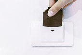 Hand holding  hotel key card insert to power switch control