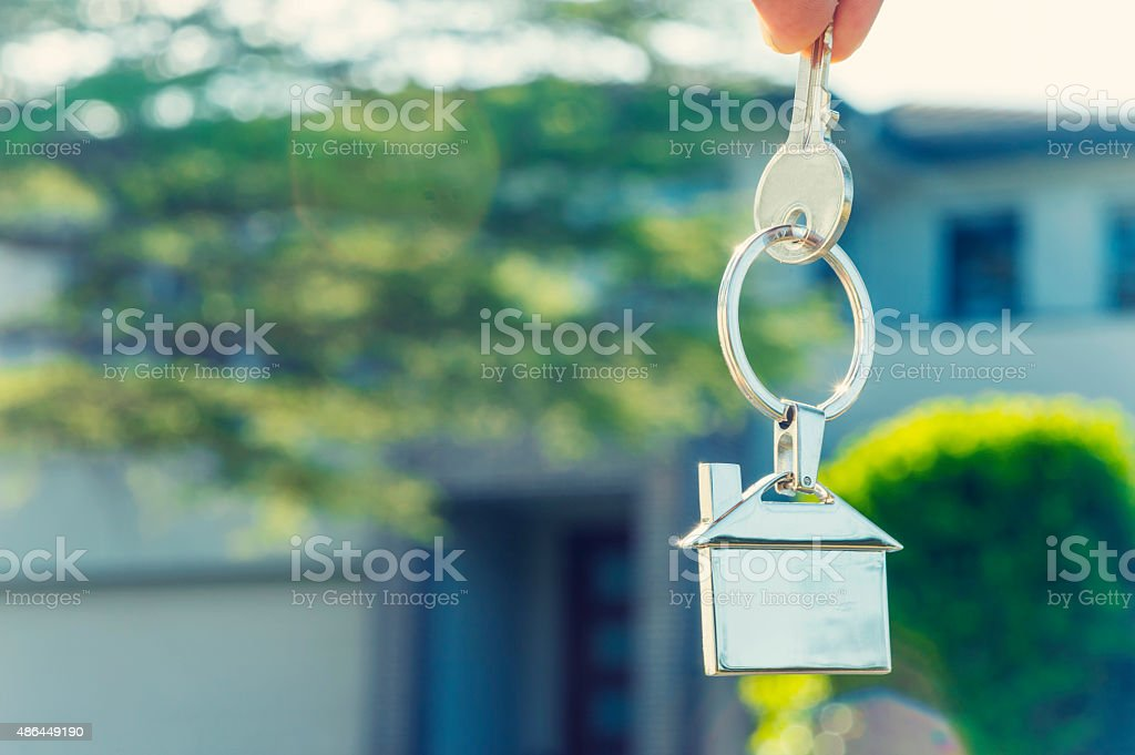 Hand holding house key in front of a large house. stock photo