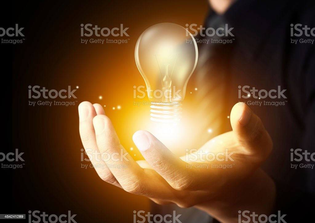 Hand holding hovering glowing lightbulb stock photo
