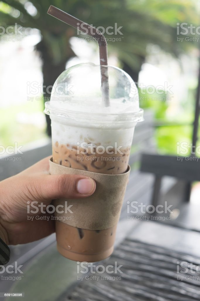 Hand holding iced coffee in coffee shop stock photo