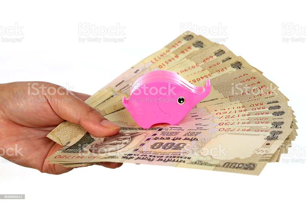 Hand holding Indian currency with piggy bank stock photo