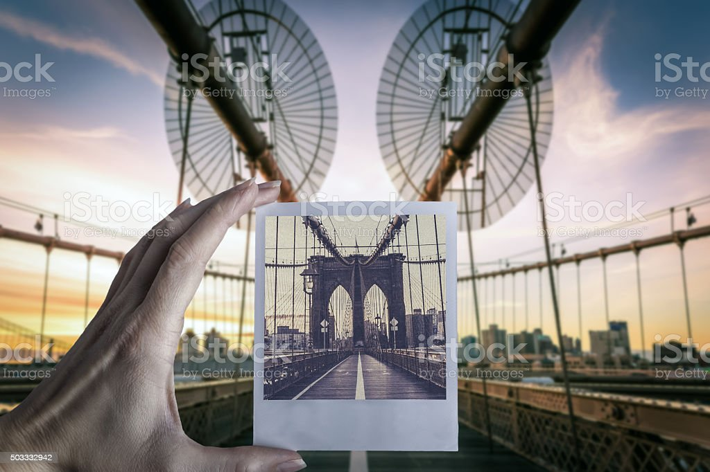 Hand holding instant camera picture at Brooklyn Bridge, NYC stock photo