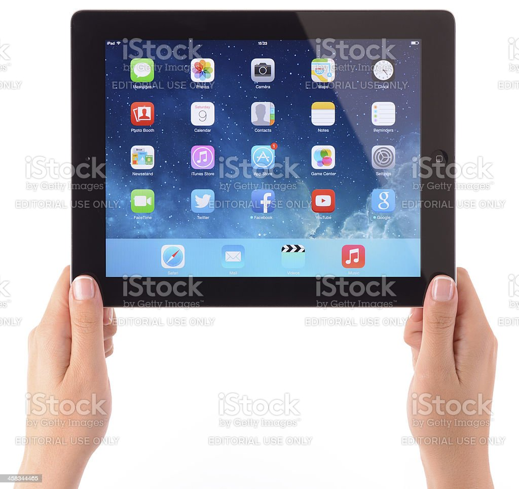 Hand holding iPad displaying iOS 7 home screen royalty-free stock photo