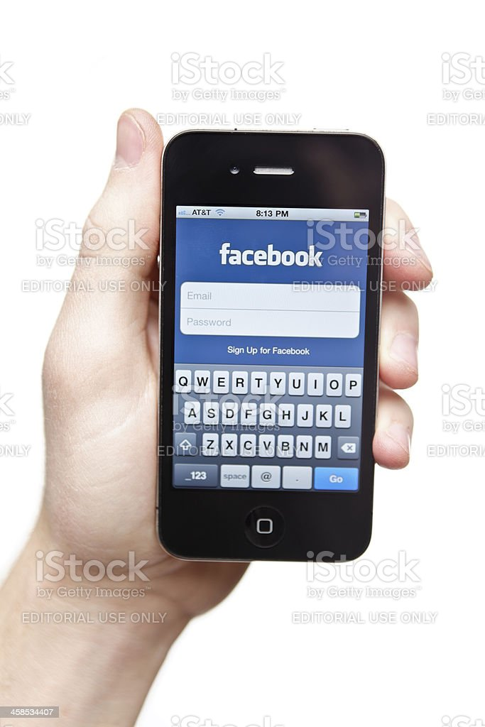 Hand holding iPhone 4 with Facebook on the screen. royalty-free stock photo