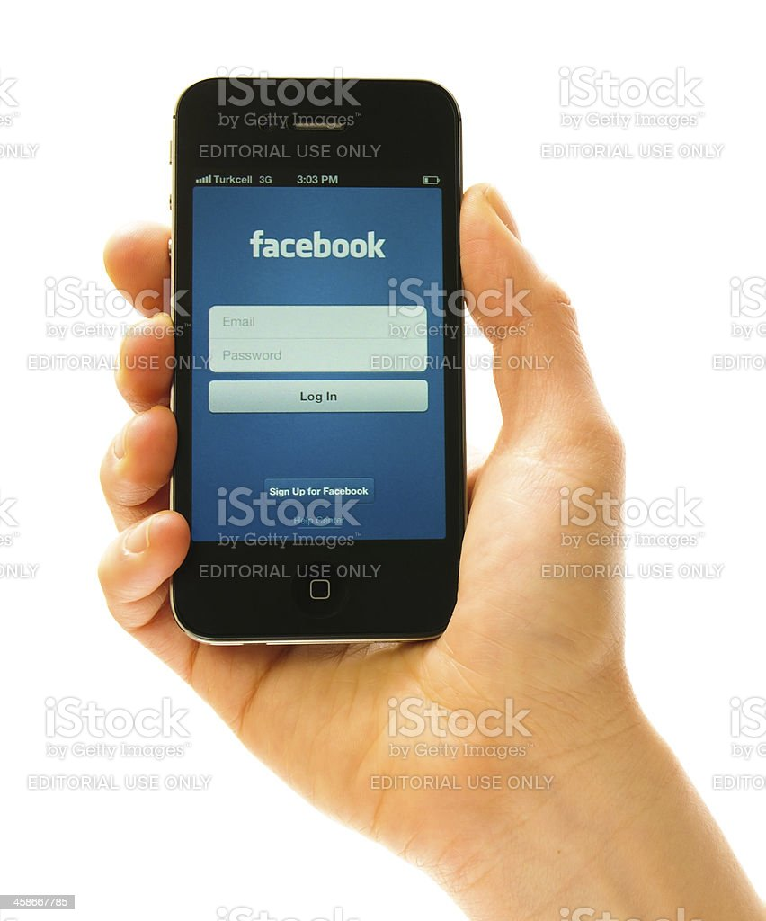 Hand holding iPhone 4s with Facebook Application stock photo