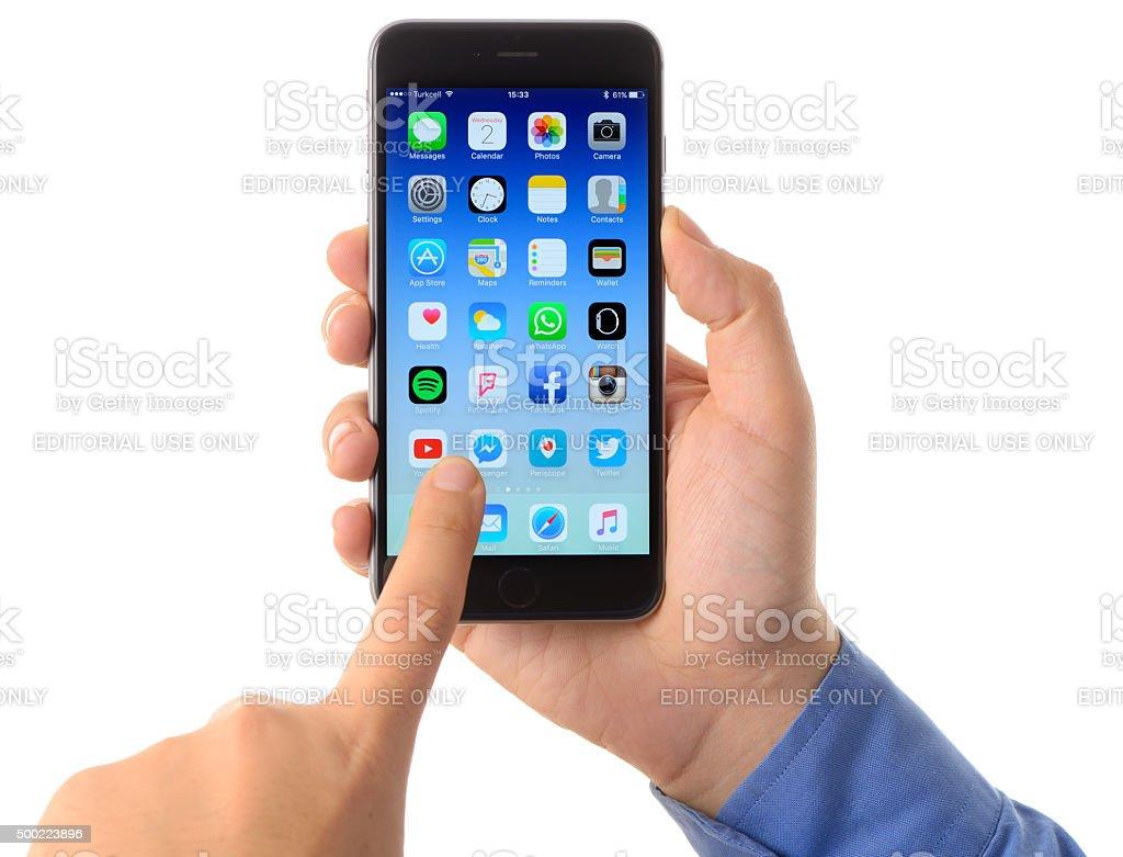 Hand holding iPhone 6 Plus on white background stock photo