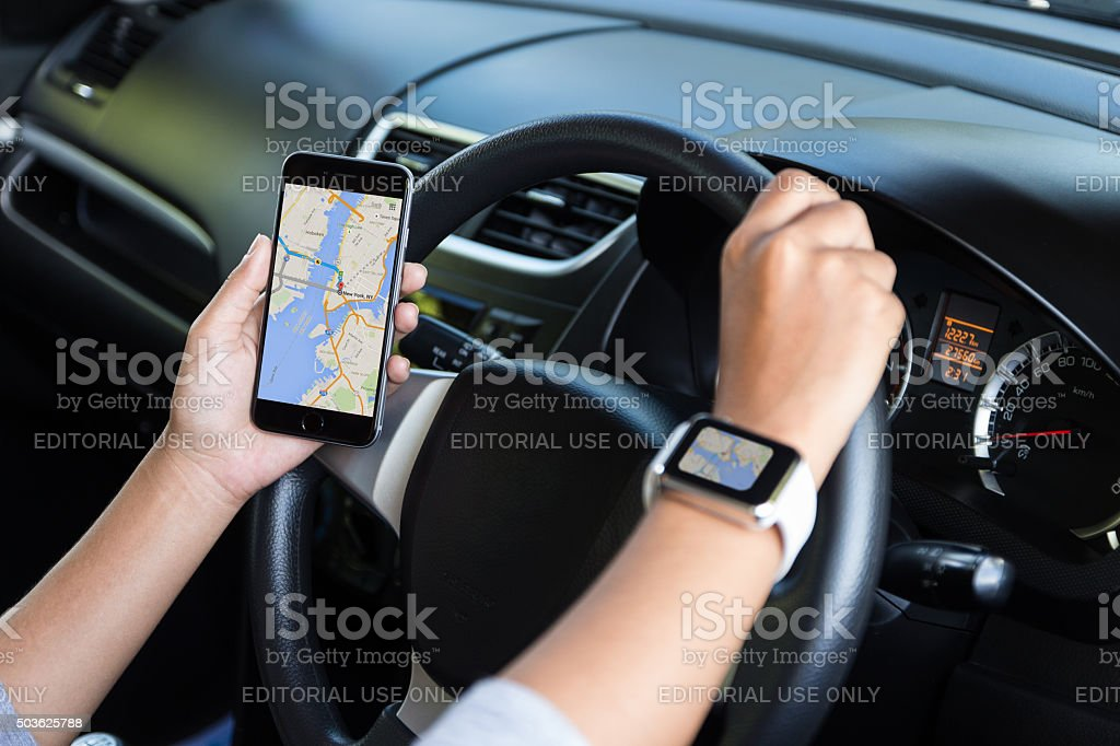 Hand holding iphone and using google map navigation in car stock photo