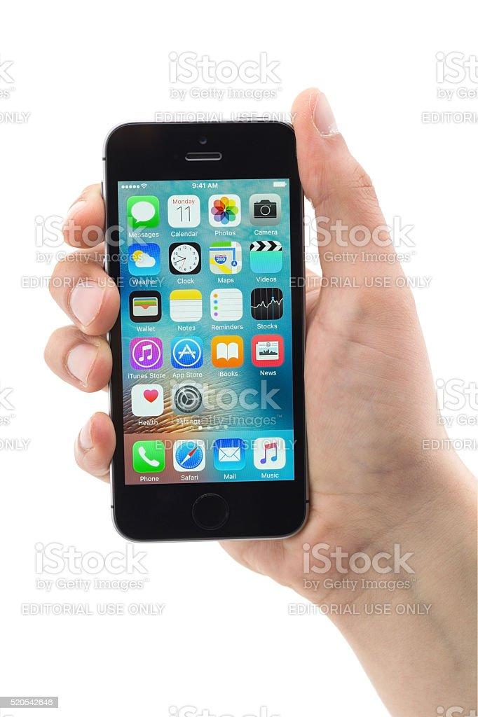 Hand holding iPhone SE isolated on white stock photo