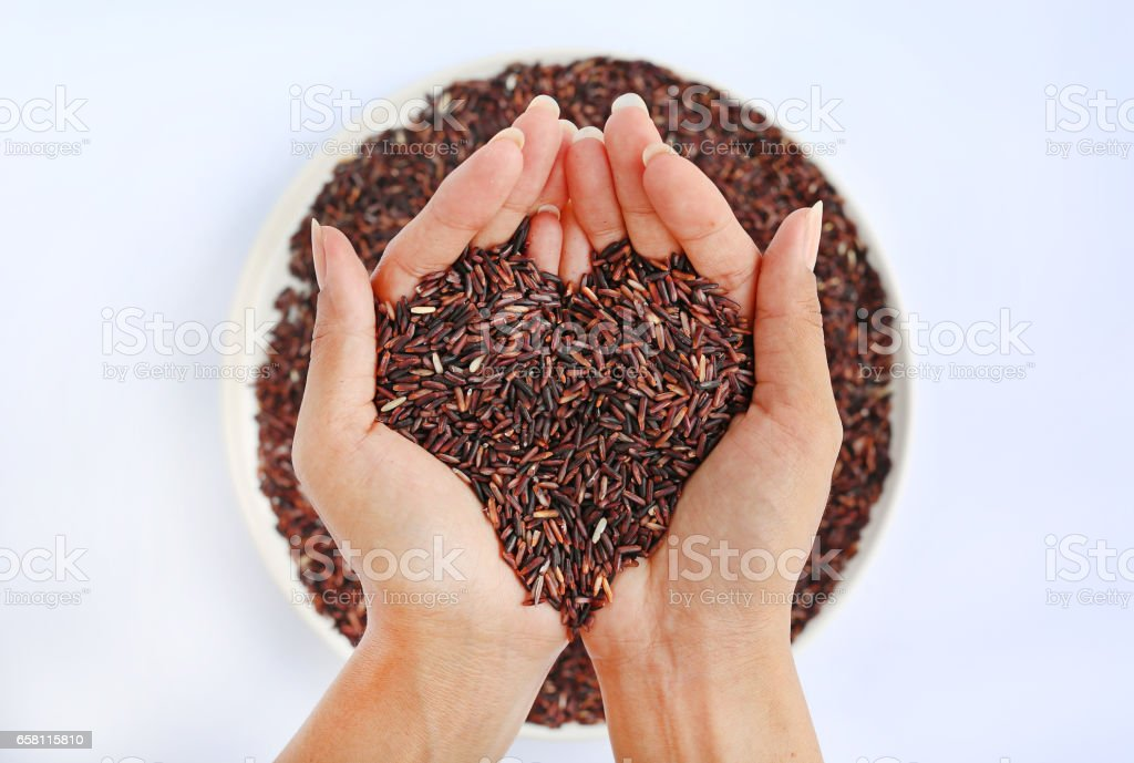 Hand holding Jasmine red rice in shape of love on white plate against white background stock photo