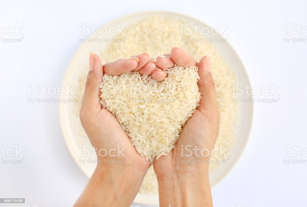 Hand holding Jasmine white rice in shape of love on white plate against white background stock photo