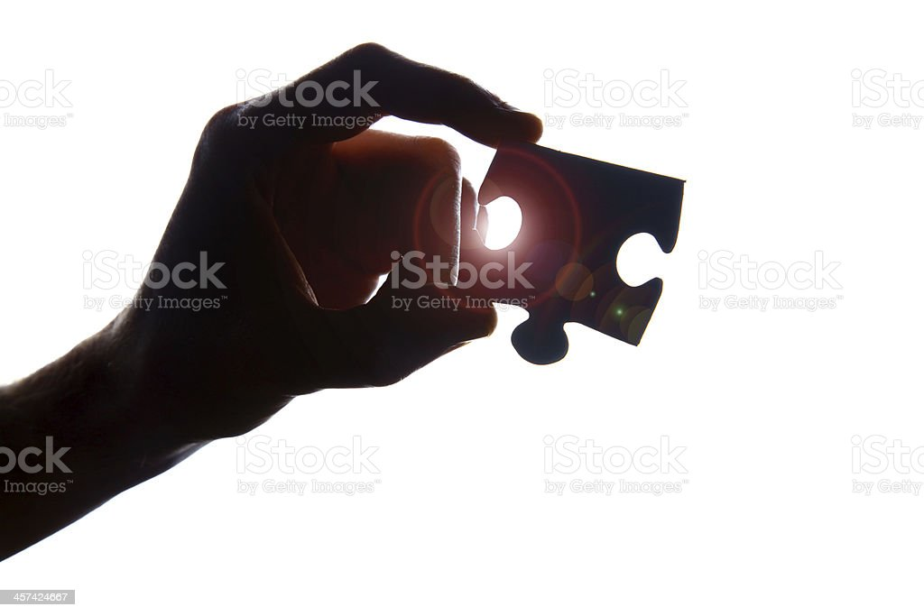 Hand holding jigsaw puzzle piece stock photo