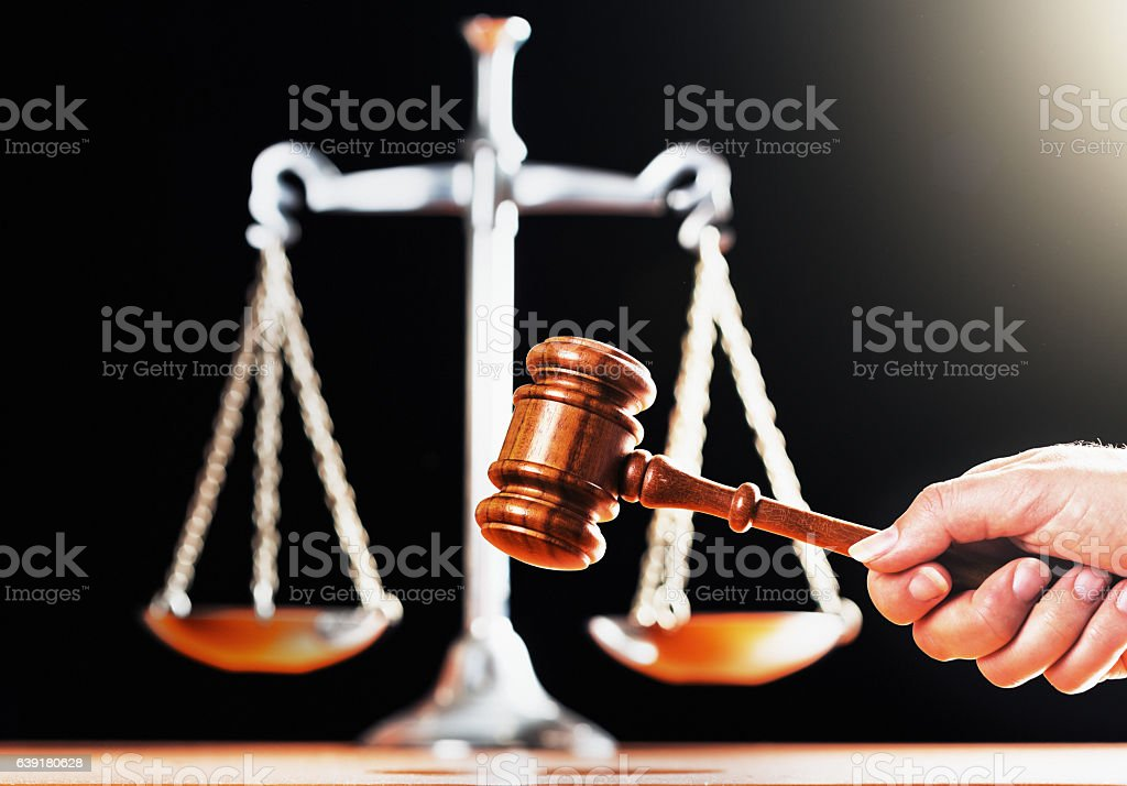 Hand holding judge's gavel by symbolic scales of justice stock photo