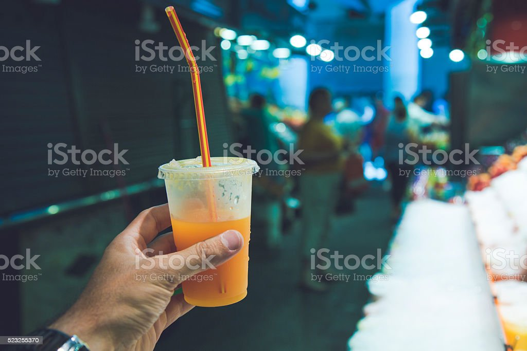 Hand holding juice in a market stock photo