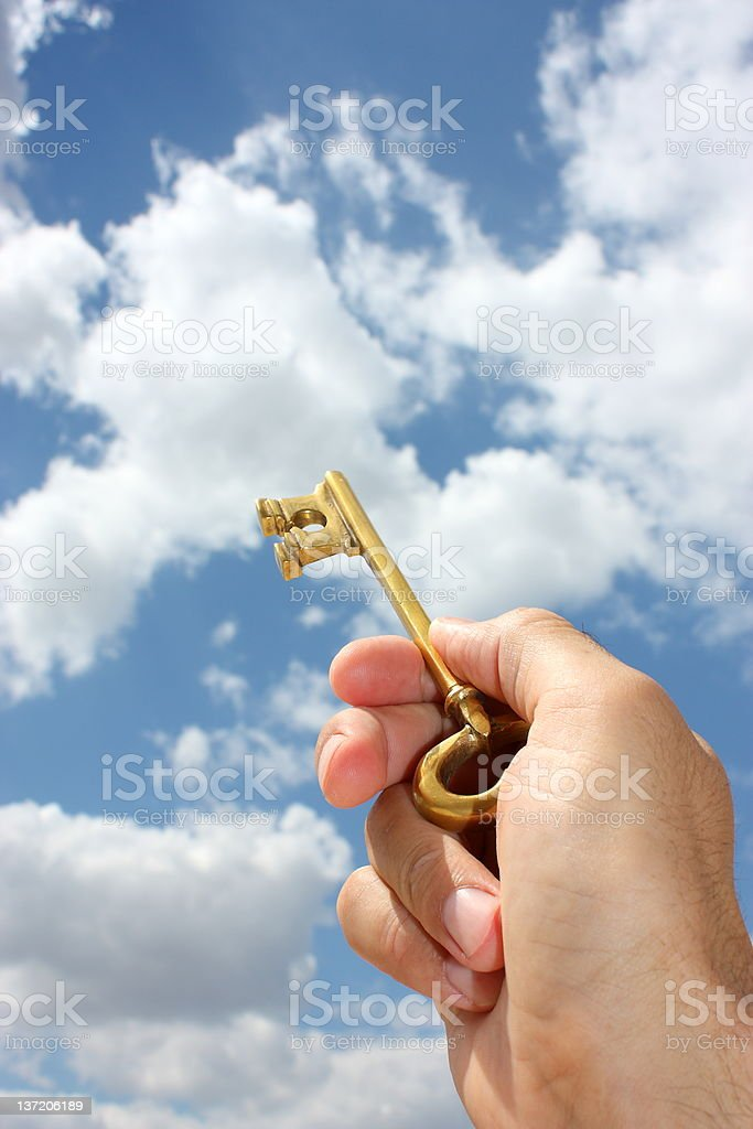 Hand holding key up to sky with clouds stock photo