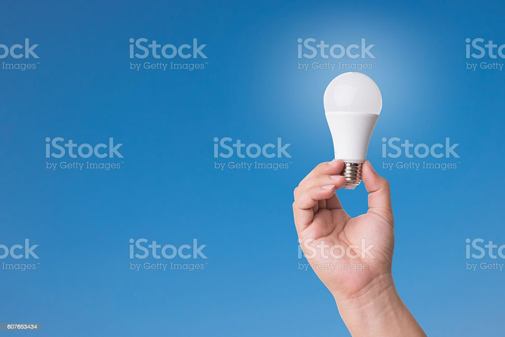 Hand holding LED Bulb with Lighting on blue sky background. stock photo