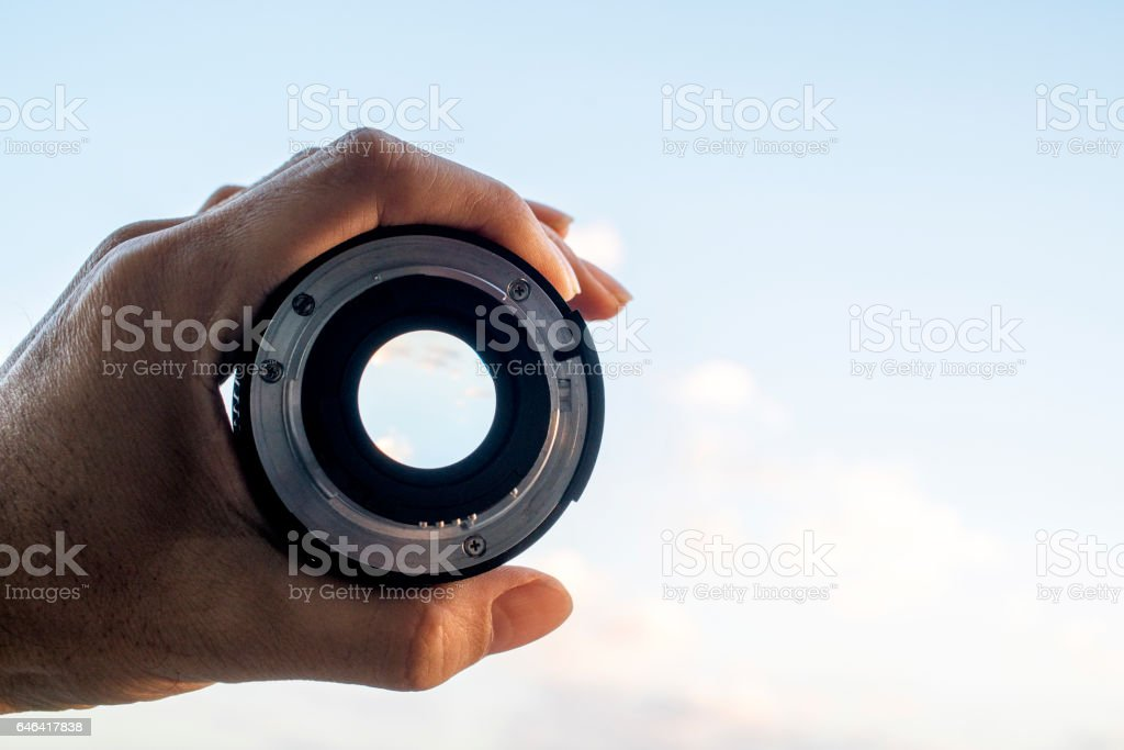 hand holding lens, looking at sky stock photo