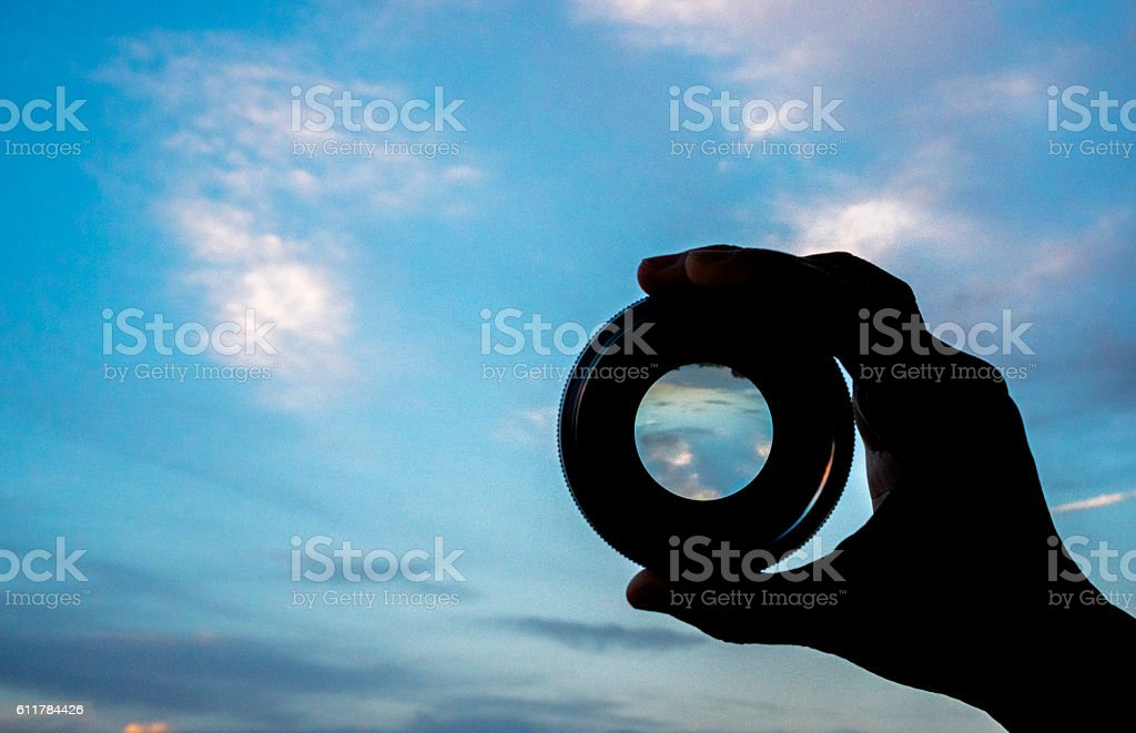 hand holding lens watching cloudscape stock photo