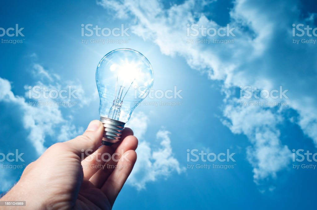 hand holding lightbulb to the sun stock photo