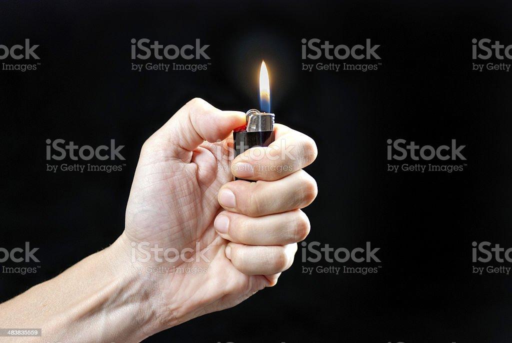 Hand Holding Lit Lighter stock photo