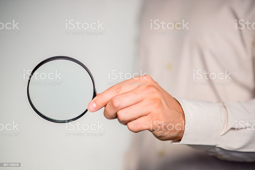 Hand holding magnifying glass isolated on gray  background, stock photo