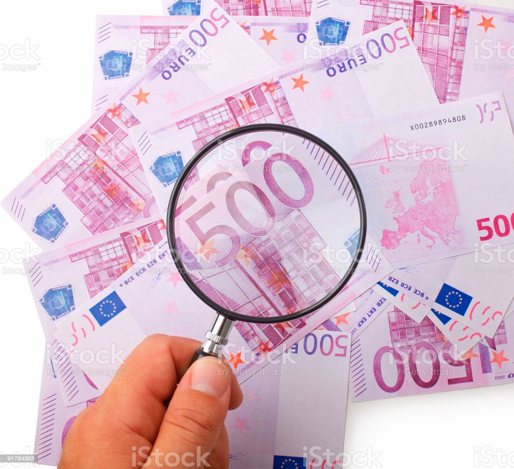 Hand holding magnifying glass over Euro notes royalty-free stock photo