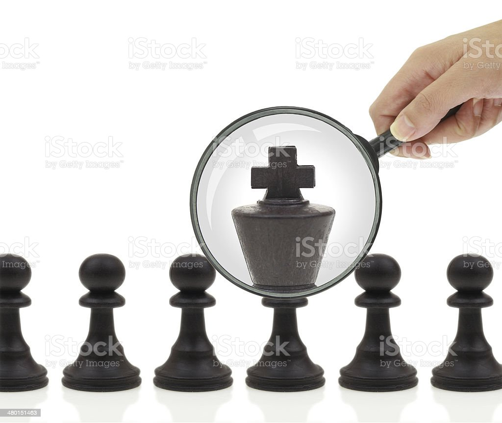 Hand holding magnifying glass over pawn who becomes king royalty-free stock photo