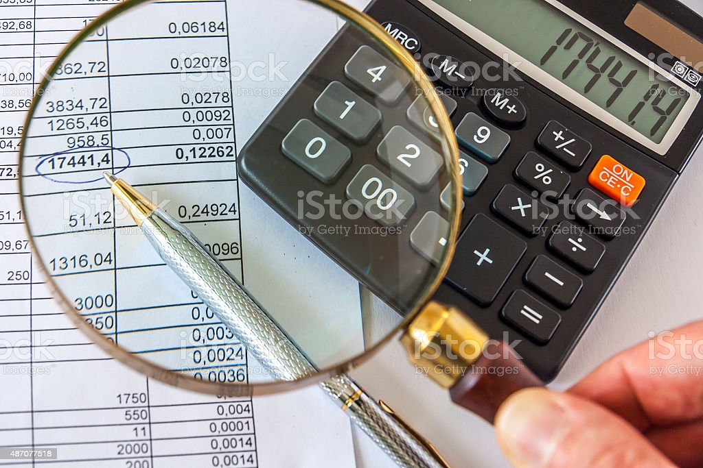 Hand Holding Magnifying Glass To Checking Business Document stock photo