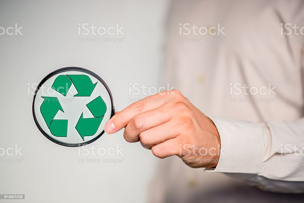 Hand holding magnifying glass  with green recycling icon stock photo