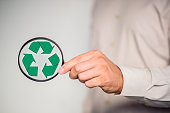 Hand holding magnifying glass  with green recycling icon