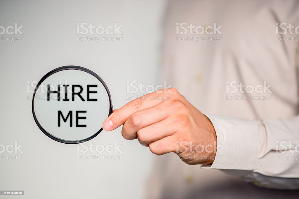 Hand holding magnifying glass with hire me sign stock photo