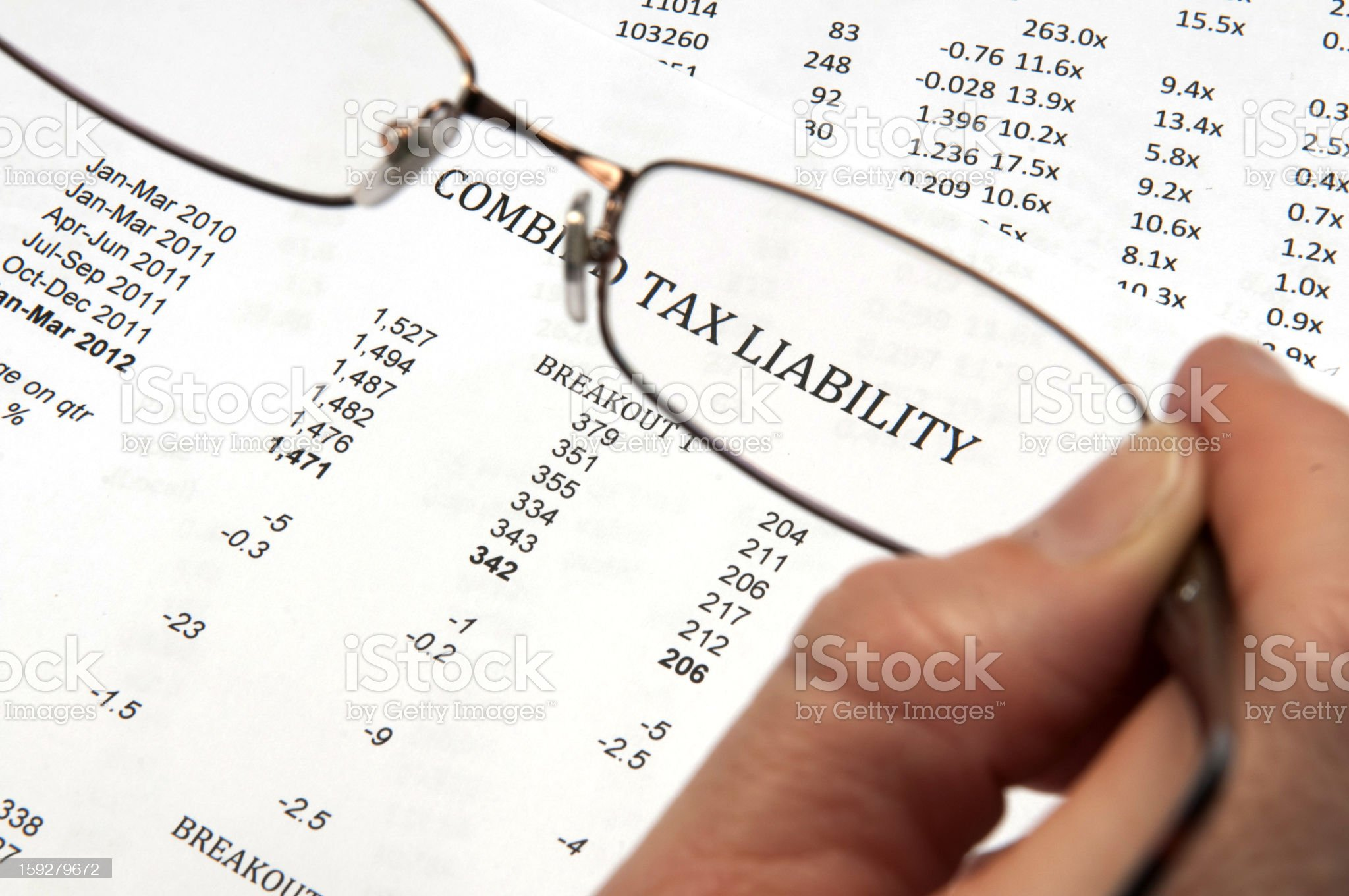 Hand holding magnifying glasses showing the words tax liability royalty-free stock photo